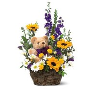 Basket of spring flowers and a teddy bear
