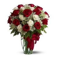 Two dozen red and white roses in a glass vase